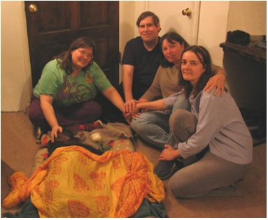 A group of four people surround the bed of Cassie, an old dog in hospice care.