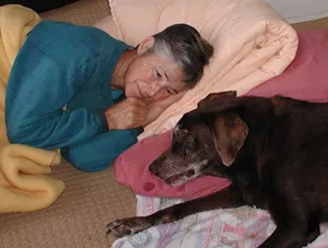 Karen and the dog Fudge lying together on blankets on the floor