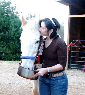 "Sandy Rakowitz of One Heart Healing Center, Virigina, kissing the senior gelding, ""Sunny"" on the head as he stands beside her eating from a metal pot"